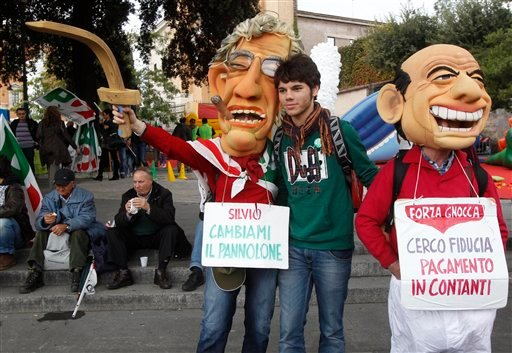 "Demonstrators wear masks mocking Italian Premier Silvio Berlusconi, right, and Reform Minister Umberto Bossi carrying placards reading: ""Silvio, change my diaper"", left, and ""I'm looking for confidence, payment in cash"" during a demonstration. (AP)"