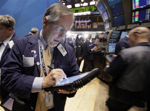 Trader Warren Meyers, left, works on the floor of the New York Stock Exchange Monday, Nov. 7, 2011.