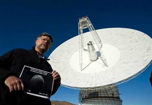 Lance Benner, research scientist at JPL displays a recent image of asteroid 2005 YU55 near the 230-foot wide radio telescope at the Goldstone Deep Space facility in Ft. Irwin, Calif., is seen, Monday, Nov 7, 2011. (AP)