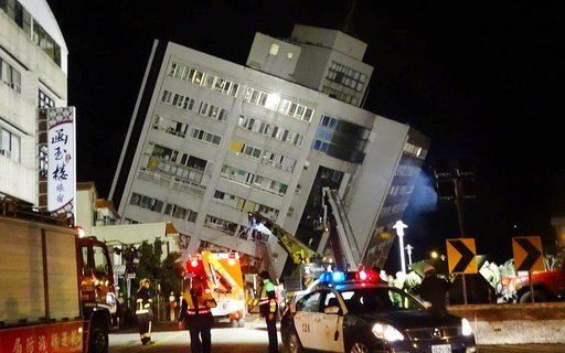 Rescuers are seen entering a building that collapsed onto its side from an early morning 6.4 magnitude earthquake in Hualien County, eastern Taiwan, Wednesday, Feb. 7 2018. Rescue workers are searching for any survivors trapped inside the building. (AP Ph