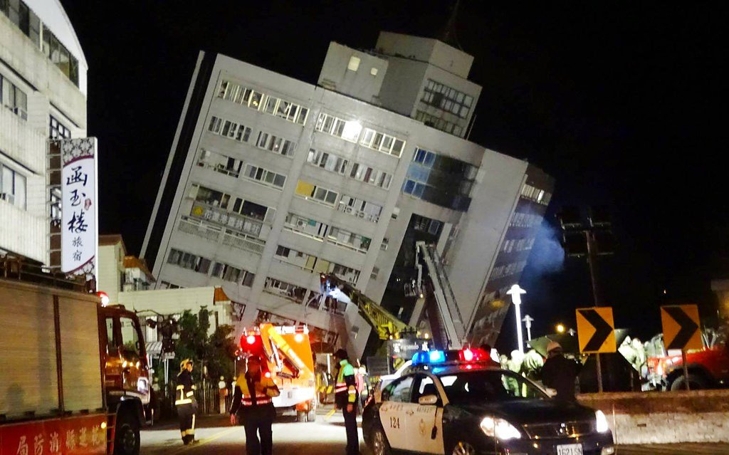 Rescuers are seen entering a building that collapsed onto its side from an early morning 6.4 magnitude earthquake in Hualien County, eastern Taiwan, Wednesday, Feb. 7 2018.  (AP Photo/Tian Jun-hsiung)