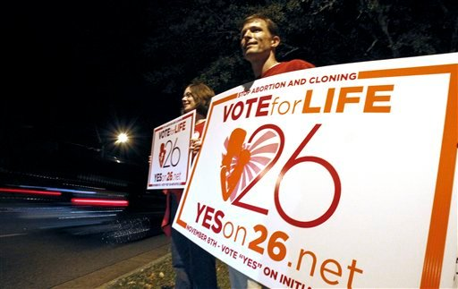 Adam Browne, right and his wife Debbie Browne, hold signs supporting a proposed amendment to the Mississippi state constitution on Tuesday, Nov. 8, 2011 in Jackson, Miss. (AP Photo/Rogelio V. Solis)