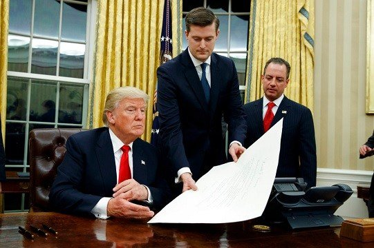 White House Staff Secretary Rob Porter, center, hands President Donald Trump a confirmation order for James Mattis.