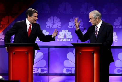 Republican presidential candidates Texas Gov. Rick Perry and Rep. Ron Paul, R-Texas, speak during a Republican Presidential Debate at Oakland University in Auburn Hills, Mich., Wednesday, Nov. 9, 2011. (AP Photo/Paul Sancya)