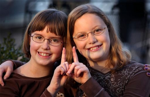 In a Monday, Nov. 7, 2011 photo, twin sisters Betsy, left, and Katie Overman pose for a photo in Madison, Wisc. The twins will turn 11 on Nov. 11, 2011, or 11/11/11.
