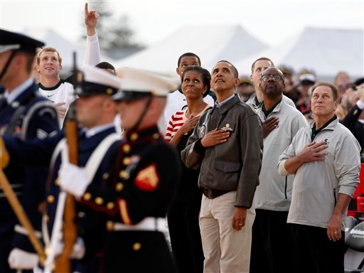 President Barack Obama and first lady Michelle Obama join Michigan State coach Tom Izzo, right, the men's basketball team as they watch a flyover from the flight deck of the USS Carl Vinson.