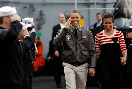 President Barack Obama salutes as he and first lady Michelle Obama walk on the flight deck of the USS Carl Vinson for the Carrier Classic NCAA college basketball game between Michigan State and North Carolina, Friday, Nov. 11, 2011, in Coronado, Calif.
