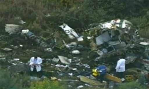 In this video frame grab image taken from Televisa's Forotv via APTN, investigators examine the wreckage of a helicopter that was carrying Mexico's Interior Minister Francisco Blake Mora, in a mountainous area of Mexico state southeast of Mexico City.