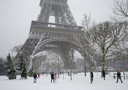People stroll on the snow-covered Champ de Mars during a snowfall in Paris, France.