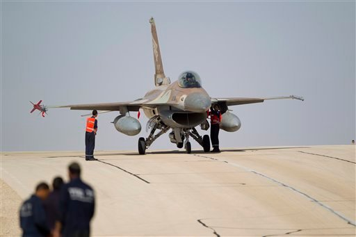 Israeli air force technicians check an Israeli air force plane F-16 of the Red Dragon squadron at Ovda airbase near Eilat, southern Israel, Monday, Nov. 25, 2013 during the Blue Flag exercise.(AP Photo/Ariel Schalit)