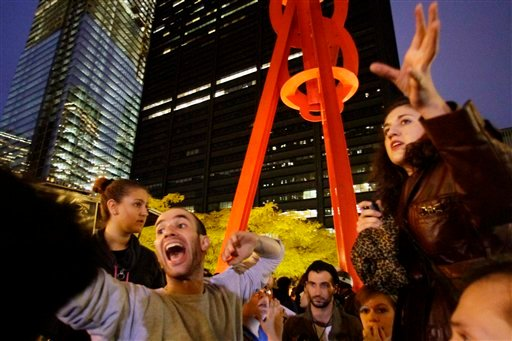 Occupy Wall Street protesters Eric Linkser, left and Cecily McMillan, right, take turns shouting information to protesters preparing to return to Zuccotti Park on Tuesday, Nov. 15, 2011, in New York. (AP Photo/Bebeto Matthews)