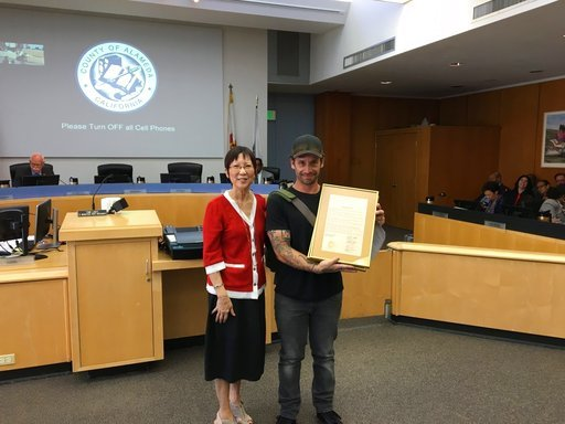 This photo provided by Alameda County, shows Alameda County Supervisor Wilma Chan presenting a Cliff Burton Day proclamation to Robert Souza, who led a petition drive that led to the board's declaration. (Courtesy of Alameda County)