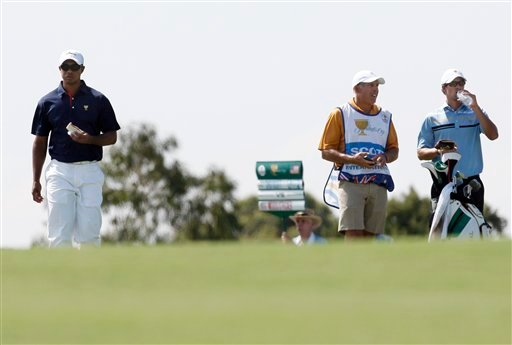 U.S. team's Tiger Woods, left, walks past his former caddie Steve Williams, second right, on the 9th fairway during the Presidents Cup golf tournament at Royal Melbourne Golf Course in Melbourne, Australia, Thursday, Nov. 17, 2011. (AP Photo/David Callow)