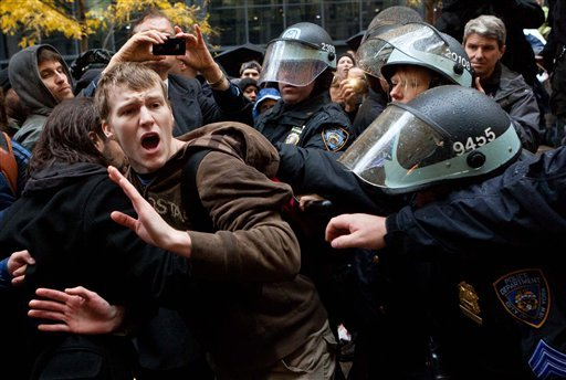 An Occupy Wall Street protestor is grabbed by police as he tries to escape a scuffle in Zuccotti Park, Thursday, Nov. 17, 2011, in New York.