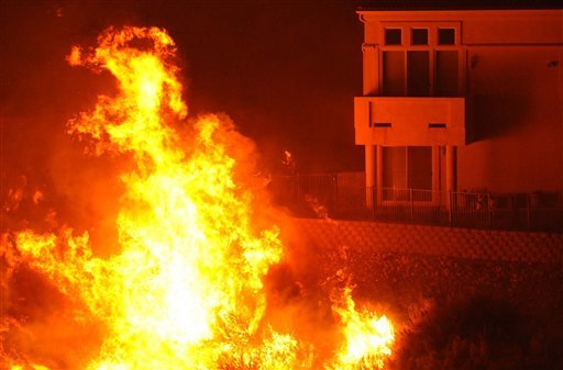 Flames surround homes in the Manzanita development of Reno, Nev. Nov. 18, 2011. Nevada firefighters are battling a wind-whipped wildfire that has already burned several homes and caused several injuries. (AP Photo/The Reno Gazette-Journal, Tim Dunn)