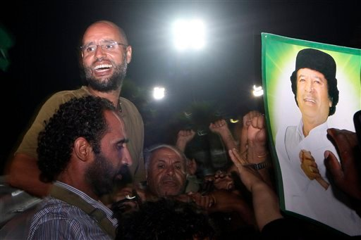 In this Tuesday, Aug. 23, 2011 file photo, Seif al-Islam Gadhafi, top left, gestures to troops loyal to his father in Tripoli, Libya. (AP)