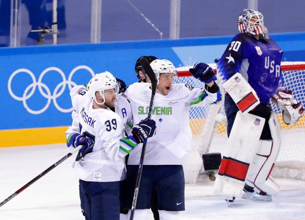 Jan Urbas (26), of Slovenia, celebrates with teammate Jan Mursak (39), as goaltender Ryan Zapolski (30), reacts after Mursak scored the game winning goal during the overtime period of the men's hockey game at the 2018 Winter Olympics