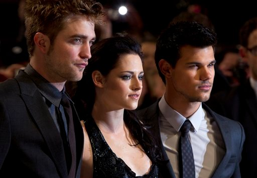 British actor Robert Pattinson, left, US actress Kristen Stewart, centre and US actor Taylor Lautner arrive for the UK film premiere of 'Twilight Breaking Dawn Part 1' at Westfield Stratford in east London, Wednesday, Nov. 16, 2011. (AP Photo/Joel Ryan)