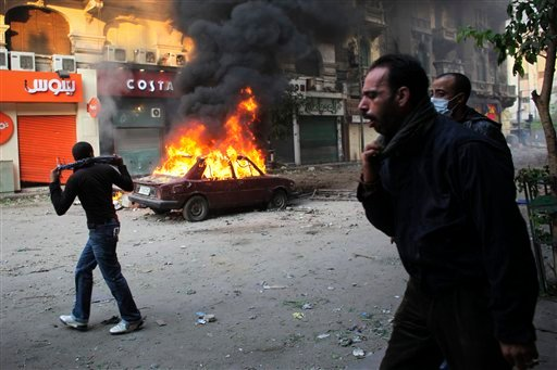 Protesters move away from tear gas fired by Egyptian riot police, not seen, during clashes near Tahrir Square in Cairo, Egypt, Monday, Nov. 21, 2011.