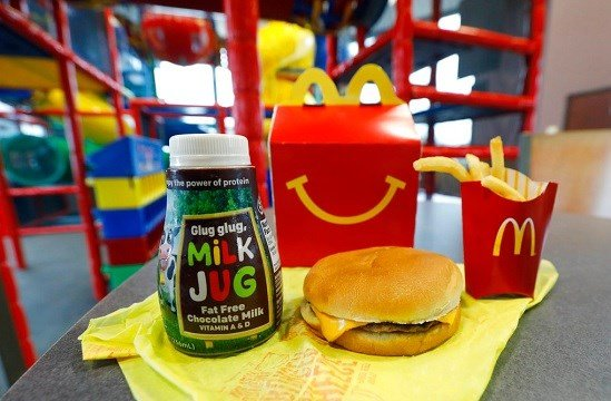 A Happy Meal featuring non-fat chocolate milk and a cheeseburger with fries, are arranged for a photo at a McDonald's restaurant.