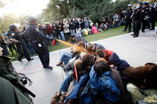 In this Friday, Nov. 18, 2011, photo University of California, Davis Police Lt. John Pike uses pepper spray to move Occupy UC Davis protesters while blocking their exit from the school's quad Friday in Davis, Calif.