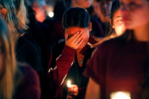 A woman cries during a candlelight vigil for the victims of the Wednesday shooting at Marjory Stoneman Douglas High School, in Parkland, Fla., Thursday, Feb. 15, 2018. Nikolas Cruz, a former student, was charged with 17 counts of premeditated murder on Th