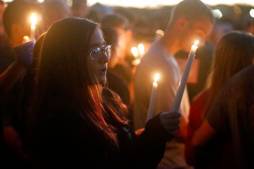 Attendees raise their candles at a candlelight vigil for the victims of the shooting at Marjory Stoneman Douglas High School, Thursday, Feb. 15, 2018, in Parkland, Fla