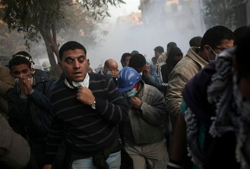 Protesters run from tear gas fired by Egyptian riot police, not pictured, during clashes near Tahrir Square in Cairo, Egypt, Tuesday, Nov. 22, 2011.