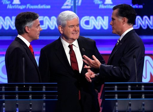 Republican presidential candidates former Utah Gov. Jon Huntsman and former House Speaker Newt Gingrich talk with former Massachusetts Gov. Mitt Romney at a Republican presidential debate Nov. 22, 2011. (AP Photo/Evan Vucci)