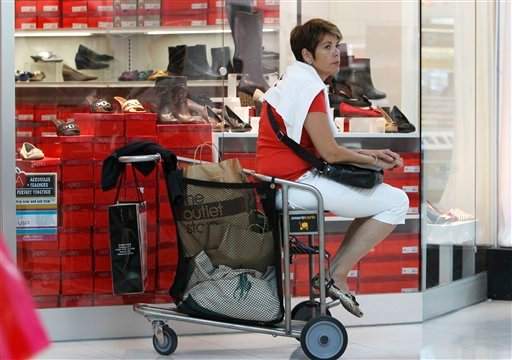 In this Nov. 9, 2011 photo, a tourist from Switzerland, who asked not to be identified, rests on her shopping cart while shopping at Dolphin Mall, in Miami. (AP Photo/Lynne Sladky)