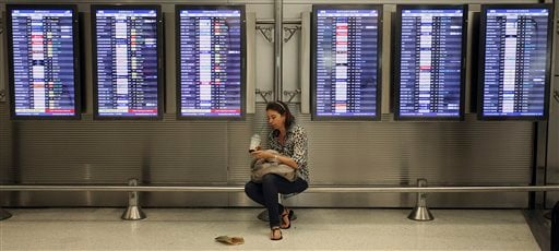 Victoria Puerto checks her flight information and tickets while waiting for her flight at the Miami International Airport in Miami Nov. 22, 2011. She was traveling today to avoid the Thanksgiving holiday rush. (AP Photo/J Pat Carter)