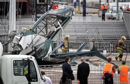 Firemen work at the scene of a helicopter accident in Auckland's Viaduct Basin, New Zealand, Wednesday, Nov. 23, 2011. (AP Photo/New Zealand Herald, Sarah Ivey)