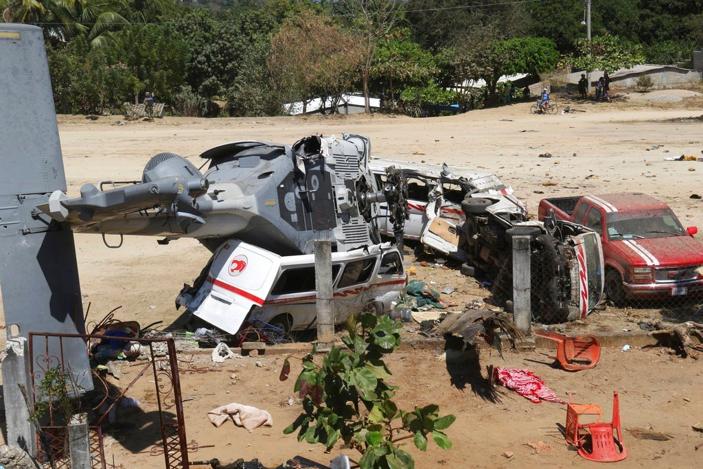 A downed helicopter lays in its side on top of a van. The military helicopter carrying officials assessing damage from the Friday's earth quake crashed killing 13 people and injuring 15, all of them on the ground. (AP Photo/Luis Alberto Cruz Hernandez)