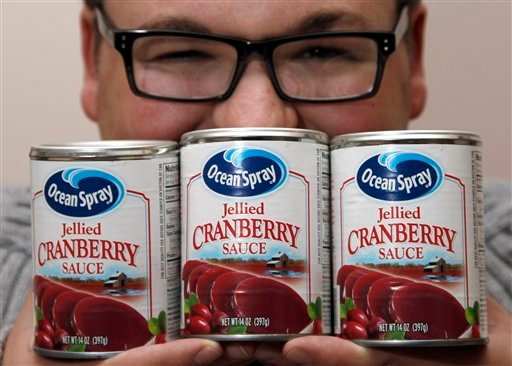Nick Mackara poses for a photograph with cans of Ocean Spray cranberry sauce Wednesday, Nov. 23, 2011 in Clementon, N.J.