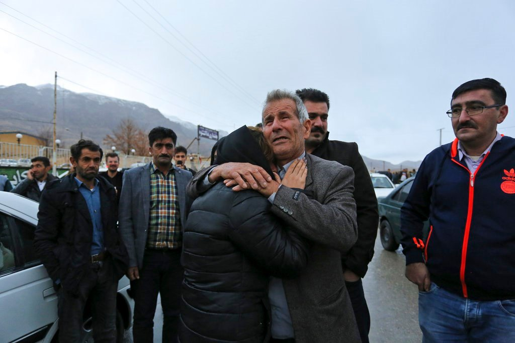 Family members of plane crash victims weep in the village of Bideh, an area near where the plane crashed, southern Iran, Sunday, Feb. 18, 2018. (Ali Khodaei,Tasnim News Agency via AP)