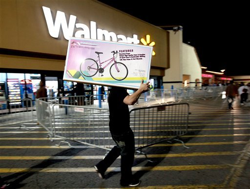 A shopper walks to his car after purchasing a bike at Walmart in Butler Plaza on Thursday, Nov. 24, 2011, in Gainesville, Fla. Walmart opened stores on Thursday.