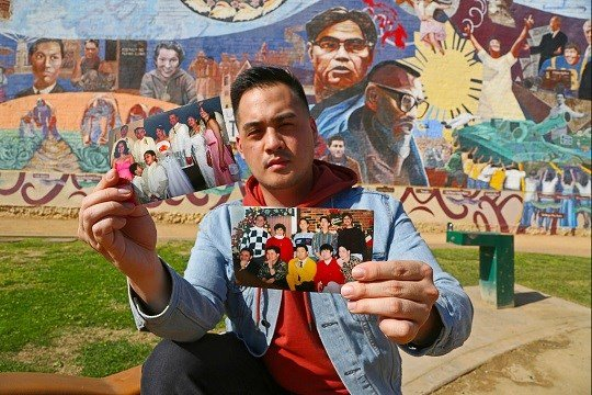 Filipino American Jeff DeGuia, 28, holds up family pictures at Unidad (Unity) Park in Los Angeles.