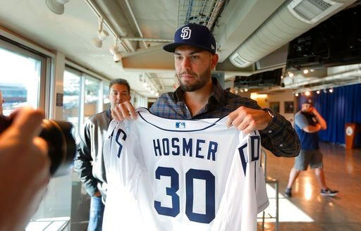 San Diego Padres baseball player Eric Hosmer poses with his jersey after an introductory press conference in Peoria, Ariz.