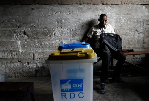 A Congolese elections volunteer stands by unsealed and empty ballot boxes nine hours after his polling station was scheduled to open in opposition candidate Etienne Tshisekedi's stronghold district of Masina in Kinshasa, Democratic Republic of Congo.