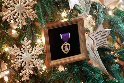 """A Purple Heart medal, and messages are seen on the official White House Christmas Tree in the Blue Room of the White House in Washington, Wednesday, Nov. 30, 2011, as the Christmas holiday decorations, whose theme is """"Shine, Give, Share"""" were previewed."""