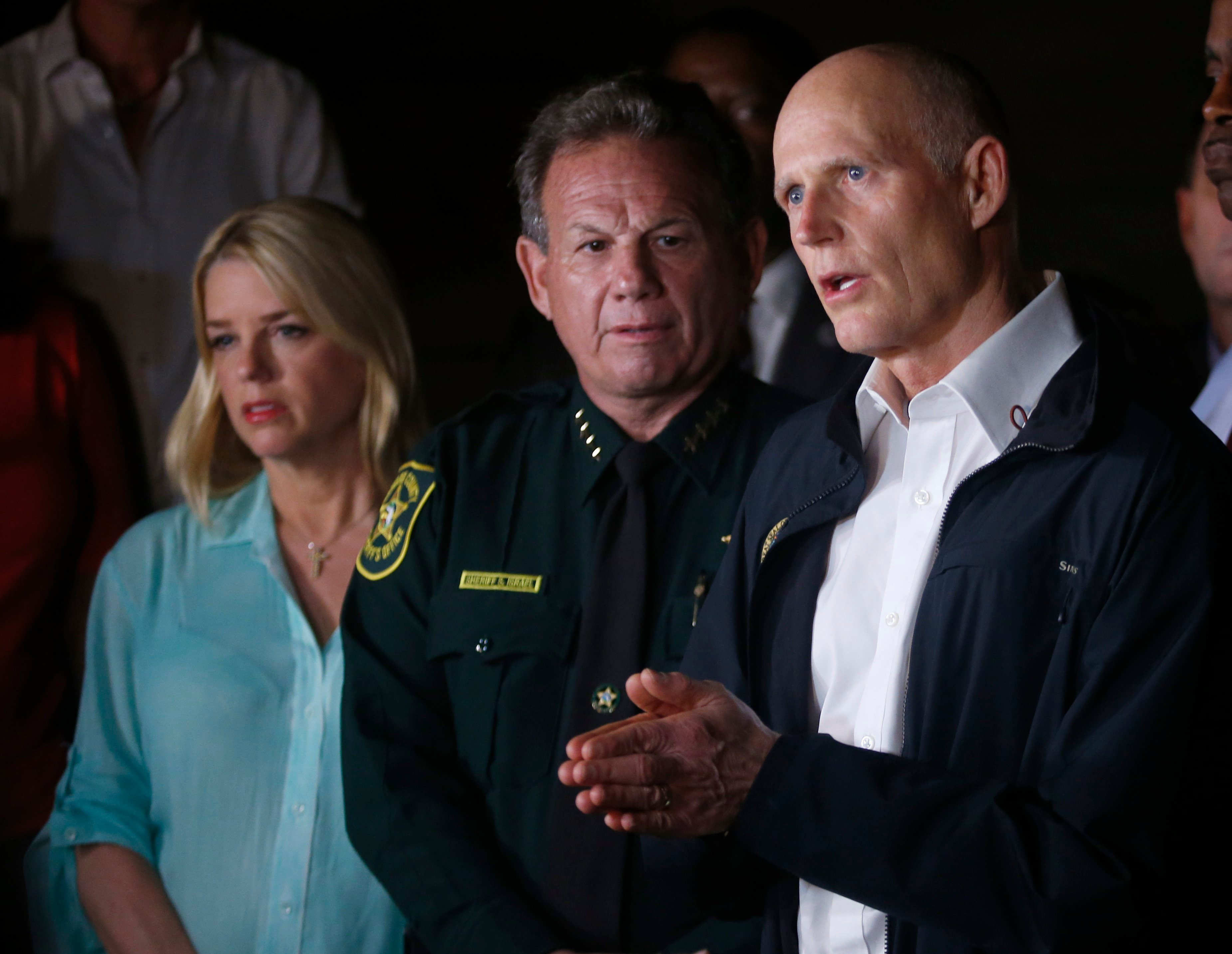 Florida Gov. Rick Scott, foreground, speaks along with Sheriff Scott Israel, center, of Broward County, and Pam Bondi, Florida Attorney General, during a news conference near Marjory Stoneman Douglas High School in Parkland, Fla. (AP Photo/Wilfredo Lee)