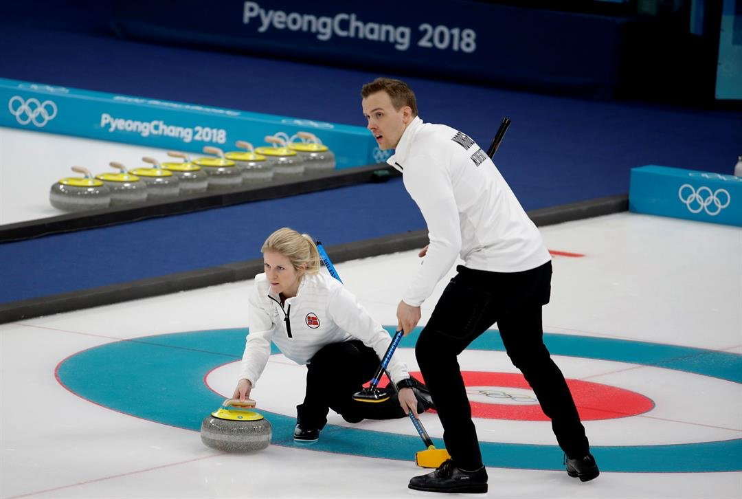 Norway's Kristin Skaslien, left, throws the stone as teammate Magnus Nedregotten looks on during the mixed doubles bronze medal curling match.
