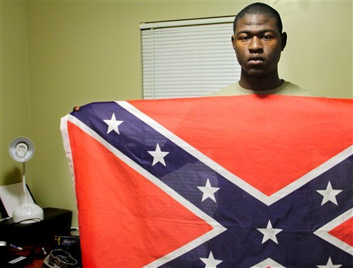 Byron Thomas, 19, a student at USCB holds a Confederate battle flag in his dormitory room on Wednesday, Nov. 30, 2011 in Okatie, S.C.
