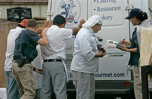 Immigration and Customs Enforcement agents search and question employees from the French Gourmet Restaurant and catering company during an immigration raid, Thursday, May 15, 2008 in San Diego. (AP Photo/Lenny Ignelzi)