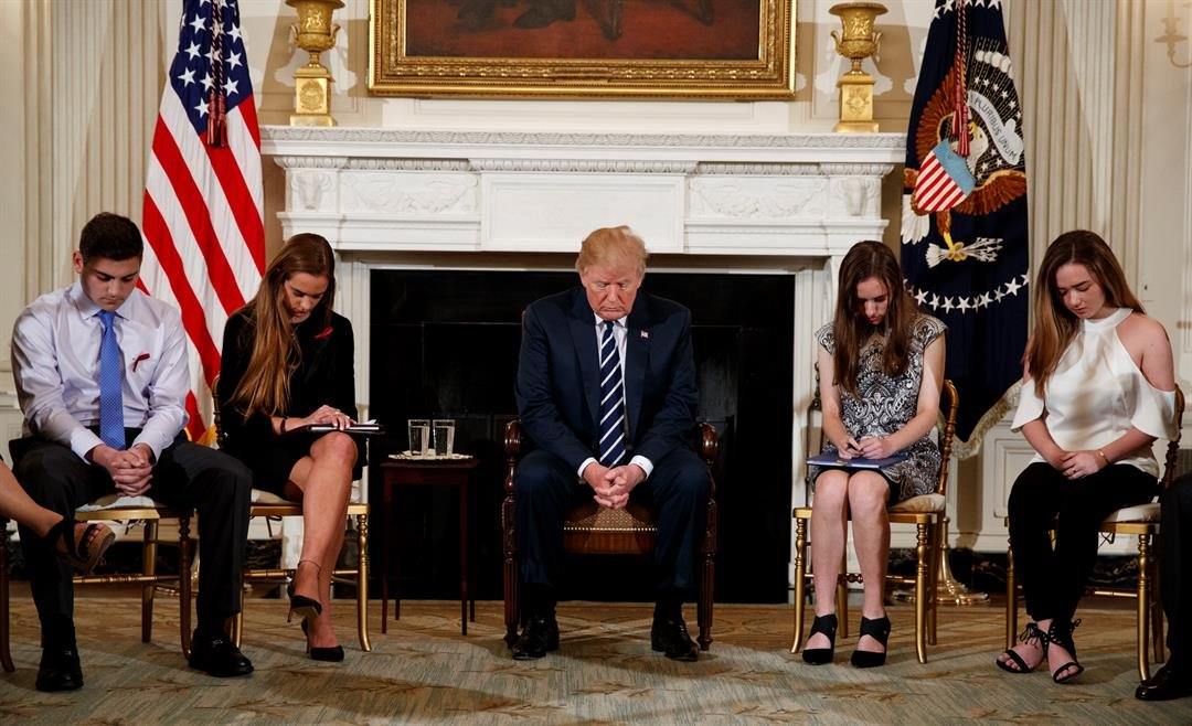 Students Jonathan Blank, Julia Cordover, Carson Abt, Ariana Klein and President Donald Trump bow their heads during the opening prayer before a listening session in the State Dining Room of the White House. (AP Photo/Carolyn Kaster)