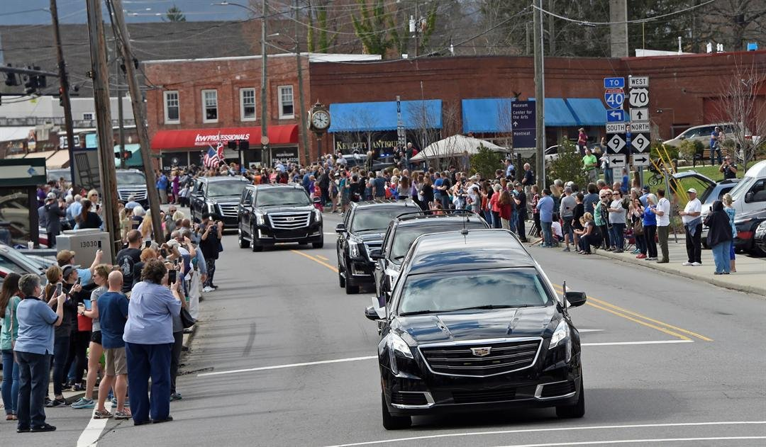 People line the street to pay respects as the hearse carrying the body of Rev. Billy Graham travels through Black Mountain, N.C. The procession is part of a week of mourning that culminates with his burial next week at his library. AP Photo/Kathy Kmonicek