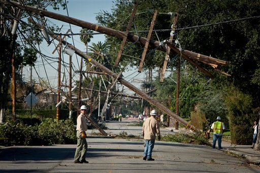 Crews from Southern California Edison power company work to clean up and restore power on Live Oak Avenue, Friday, Dec. 2, 2011, in Temple City, Calif.