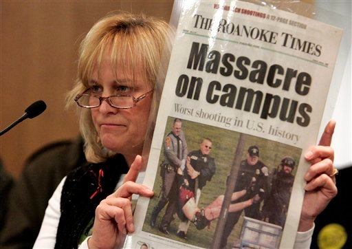 In this Jan. 21, 2008, file photo Suzanne Grimes holds up a picture of her injured son, Virginia Tech shooting victim Kevin Sterne, during a Senate Courts of Justice committee hearing on a bill to close the gun show loophole at the Capitol in Richmond, Va