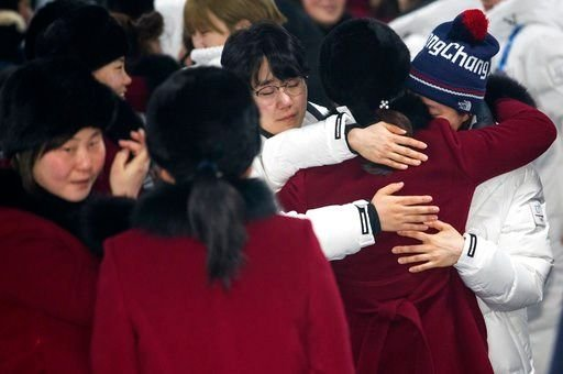 A North Korean women's hockey team player hugs her South Korean teammates, wearing white coats, before returning to North Korea, at Olympic Village in Gangneung, South Korea, Monday, Feb. 26, 2018.