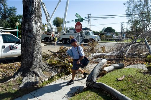 Despite the downed trees posing obstacles postal worker Edward Tena delivers mail along Live Oak Ave., in Temple City, Calif., on Saturday, Dec. 3, 2011.